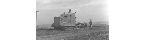 Armoured tractor ploughing land